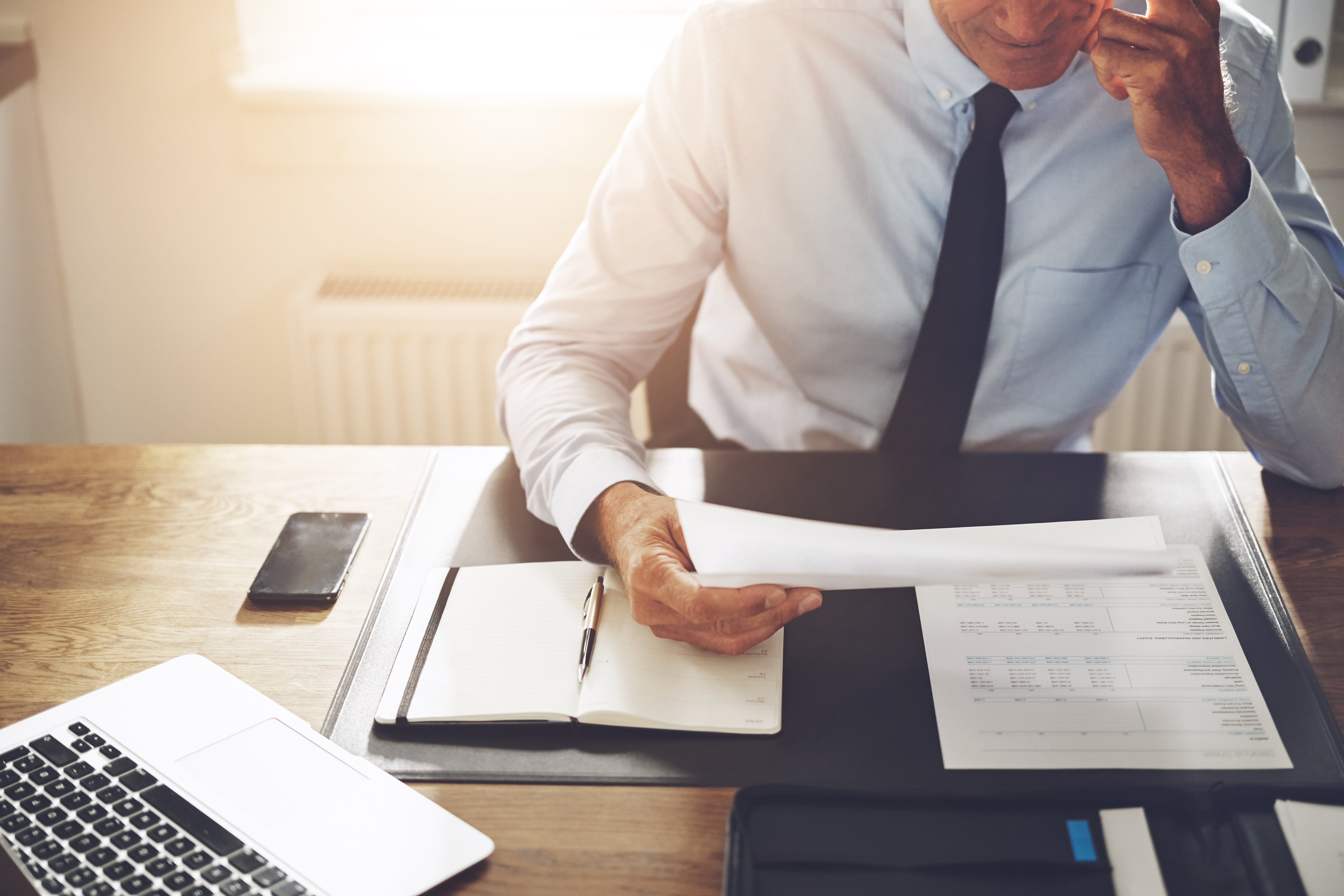 businessman-sitting-at-an-office-desk-reading-QAWYC7B.jpg